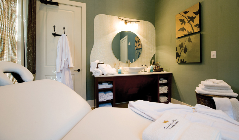 Luxurious spa room and serene massage table. Earthy green wall & a marble basin sink.